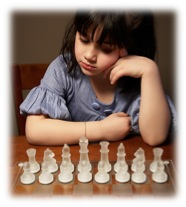 Girl staring at chess pieces on a board