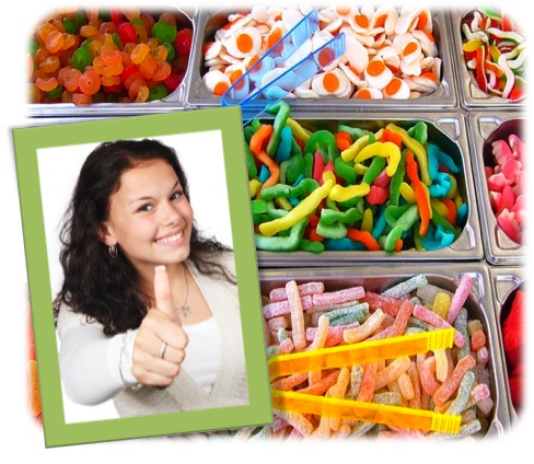 "Woman giving a ""thumbs up"" to an assortment of candy products"