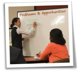 Instructor writing problems and opportunities on a white board