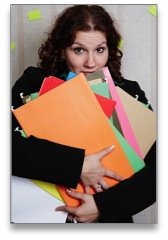 Overwhelmed business woman holding an armful of files